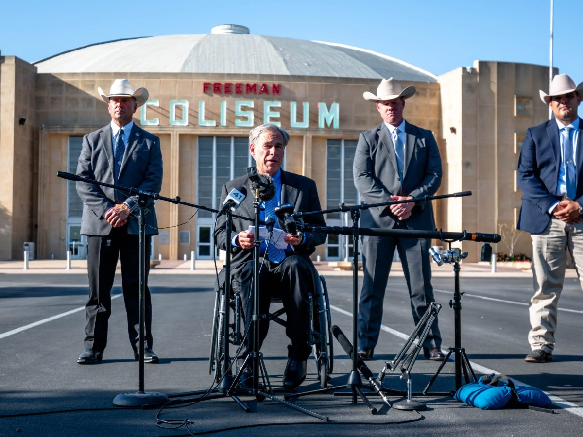 Governor Greg Abbott address members of the media during a press conference outside of the Freeman Coliseum where more than 1,600 migrant children are being held. Texas Rangers stood in a line behind the Governor during the press conference.