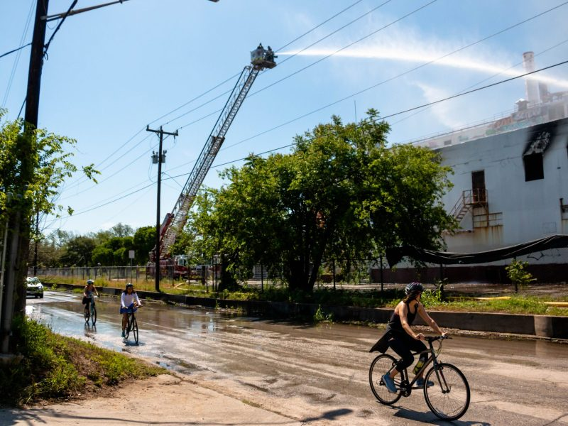 Cyclists slow down to see firefighters douse the former Lone Star Brewery building Sunday morning.