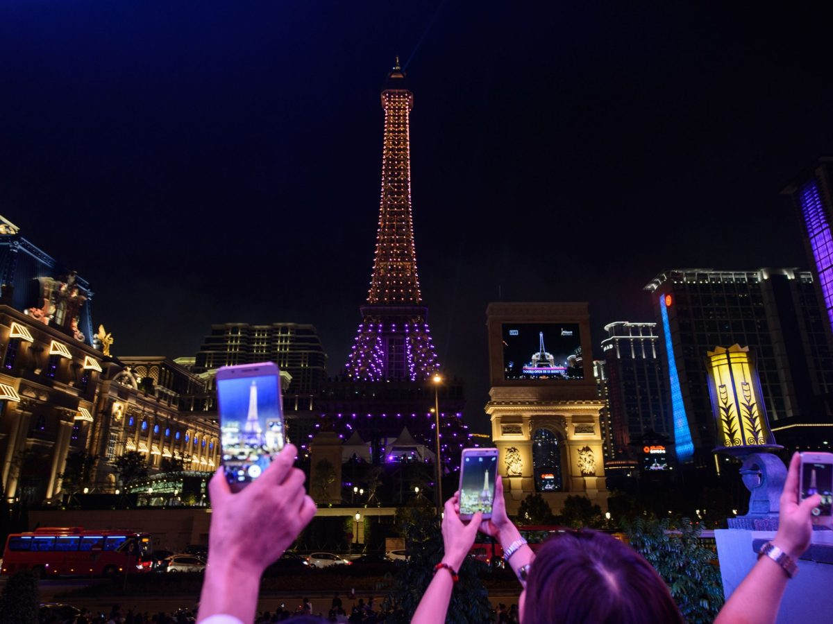 People take photos of an Eiffel Tower replica after the 2016 opening of The Parisian, a Sands resort in Macau.