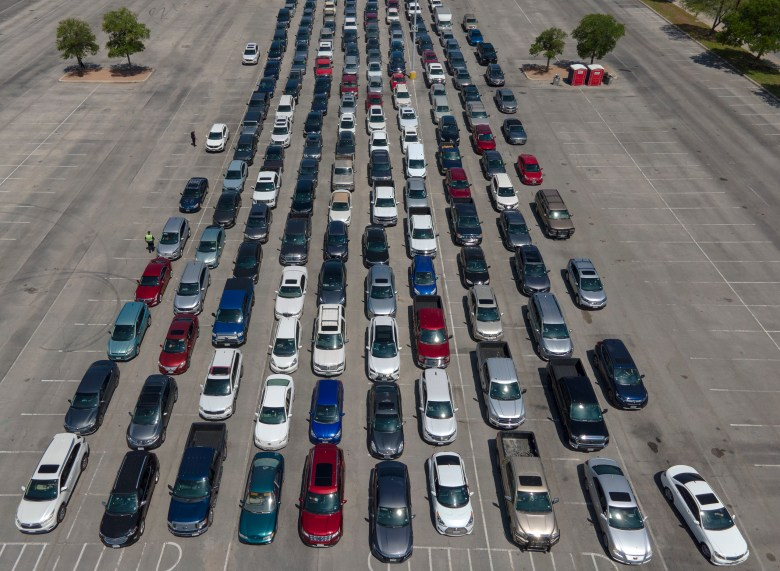 Hundreds of people wait to receive their drive-up vaccination for COVID-19 at the Alamodome in April.