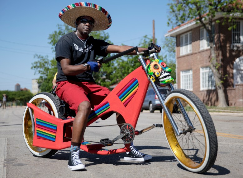 Phillip Johnson poses for a photo with his custom-made bike during the inaugural Fiesta Bike Parade on Saturday.