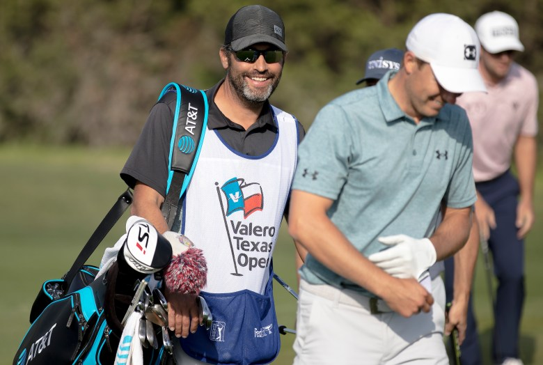 Caddy Michael Greller laughs with Jordan Spieth after Spieth hit the pin with a chip shot on the seventeenth hole during the Texas Open at TPC San Antonio on Friday.