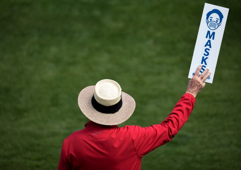"""A golf marshal holds up a sign reading """"masks required"""" during the Texas Open at TPC San Antonio on Friday."""