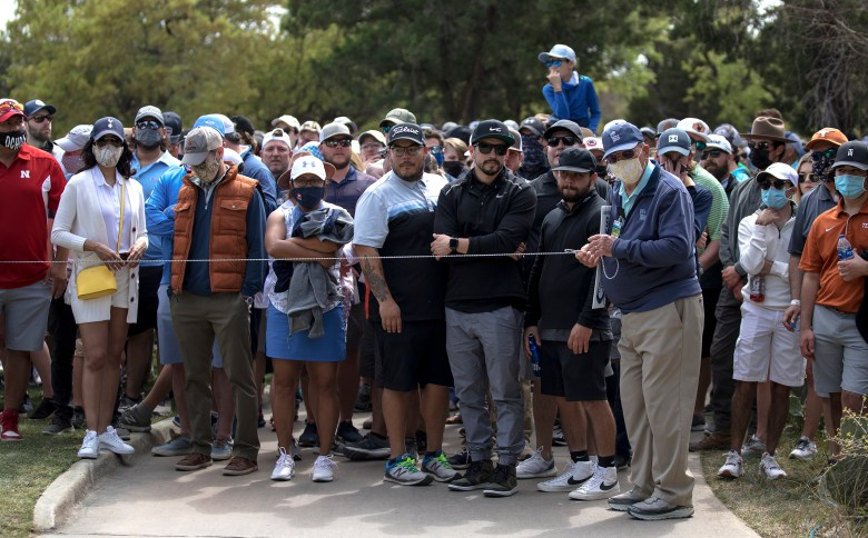 Spectators wait for golfers to pass before walking to the next tee box during the Texas Open at TPC San Antonio on Friday.