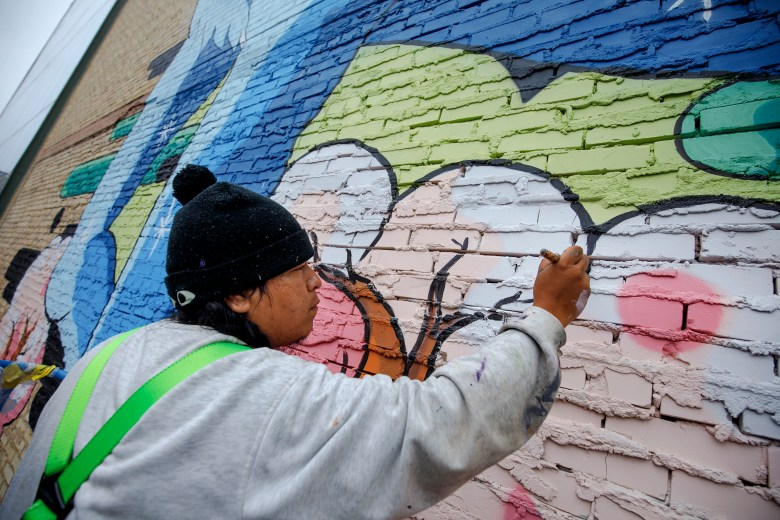 """Muralist Rudy Herrera adds finishing touches to his mural titled """"The Last Parade"""" on Saturday."""