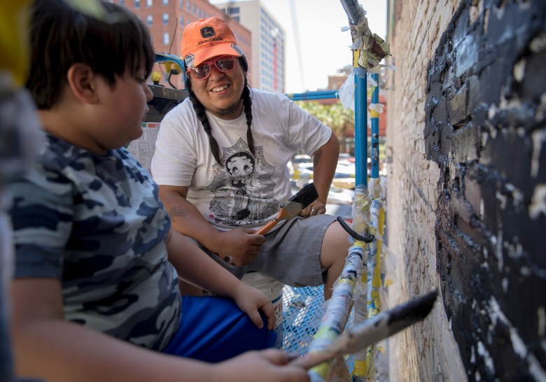 Muralist Rudy Herrera adds the finishing touches to his mural with his son, Rocco, on Saturday.