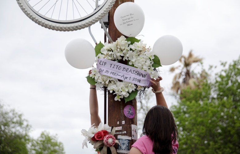 Sylvia Dinger helps hang a wreath during an event honoring bicyclist Tito Bradshaw on Saturday. Bradshaw, a beloved local cyclist, was struck and killed by an alleged drunk driver on April 1, 2019, on East Houston Street. Family members and friends gathered to demand justice for Tito and urge city officials to approve a bike-safe infrastructure plan.