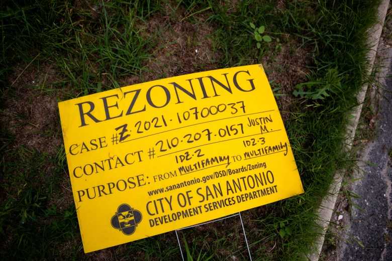 A rezoning sign lays in the grass next to the property on 318 W Grayson.
