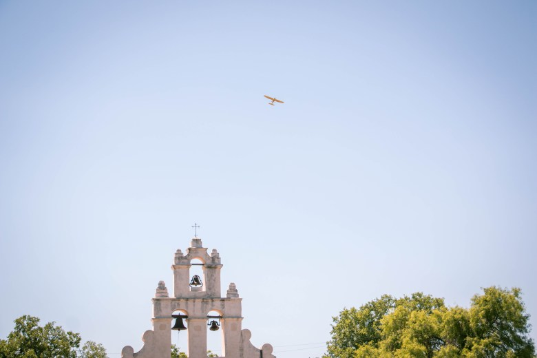 A plane flies over the church in the center of Mission San Jose. The Stinson Municipal airpot is a short distance behind the mission.