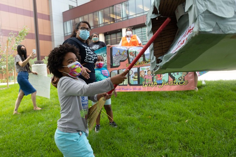 A piñata representing the Deely Coal Plant is smashed by activists as it is hung on a tree in front of the CPS Energy headquarters on Monday.