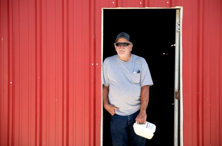 Miller Farms owner Eddie Miller poses for a portrait outside of his honor-system raw milk shop in La Coste, Texas.