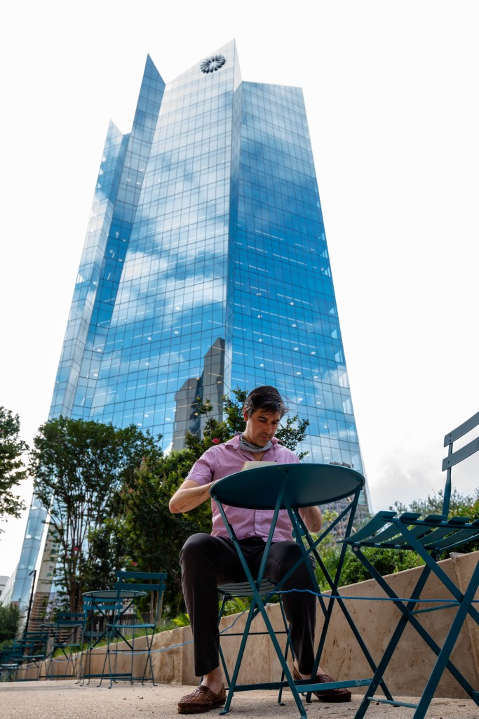 David writes in his journal while sitting at Legacy Park next to the Frost Tower. Over the eight years he's lived downtown he's watched the area evolve and develop.