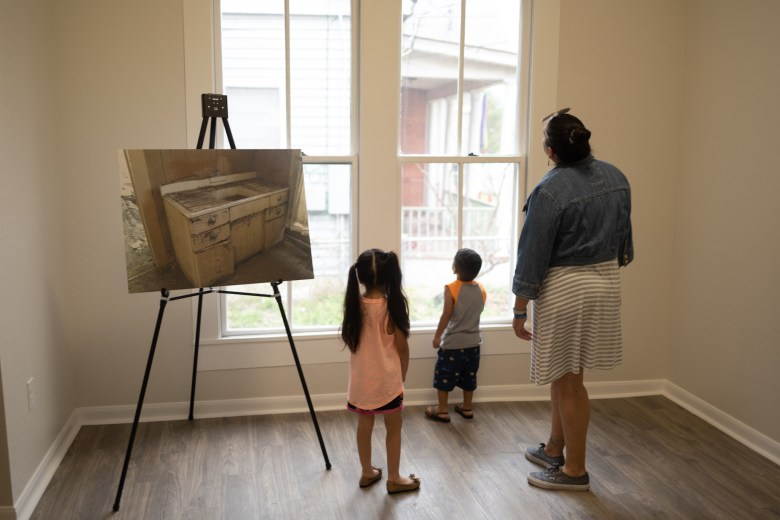 Visitors of the home look through the large windows that now fill the interior of the home with light.