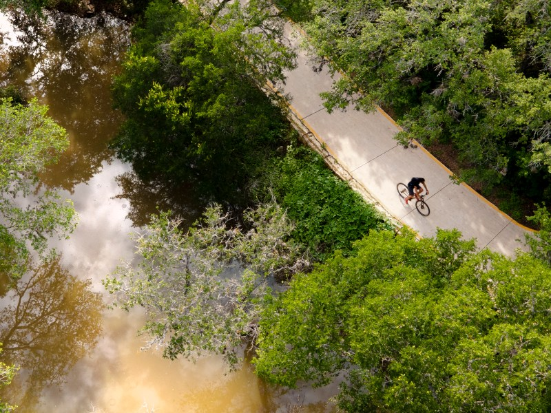 A bicyclist rides south on the Salado Creek Greenway trail, which is a part of the greater Howard W. Peak Greenway Trails System.