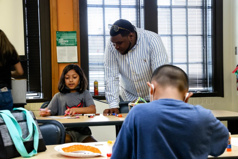 Founder of Essence Prep, Akeem Brown, asks Frances Miramontes, 8, about her drawing in the arts and crafts room at Ella Austin Community Center. The new charter school has partnered with Ella Austin to engage children in the east side in educational and fun activities during the summer.