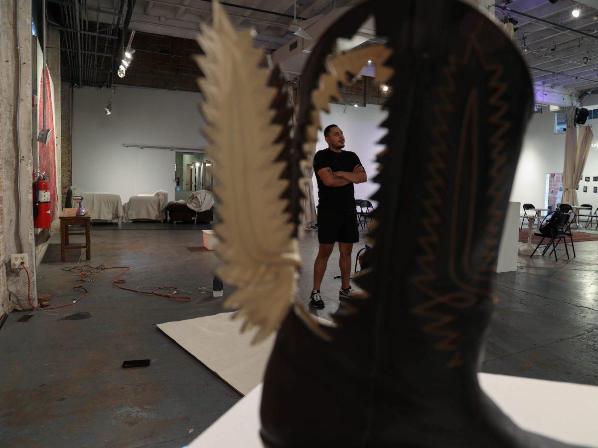Jose Villalobos is seen through a cutout through his boot sculpture titled Bota Para Llegar al Cielo.