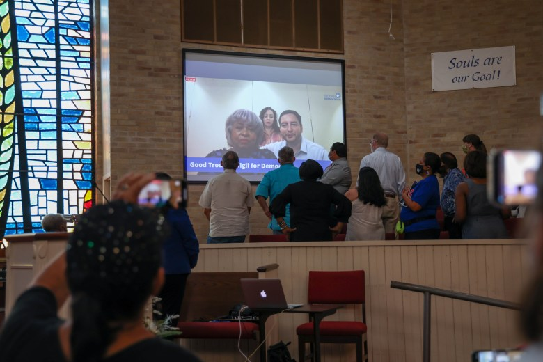 Barbara Gervin-Hawkins (left) speaks alongside Representatives Liz Campos (center) and Phillip Cortez (right), via a video call to attendees of the Voting Rights Vigil at Friendship Baptist Church Saturday.