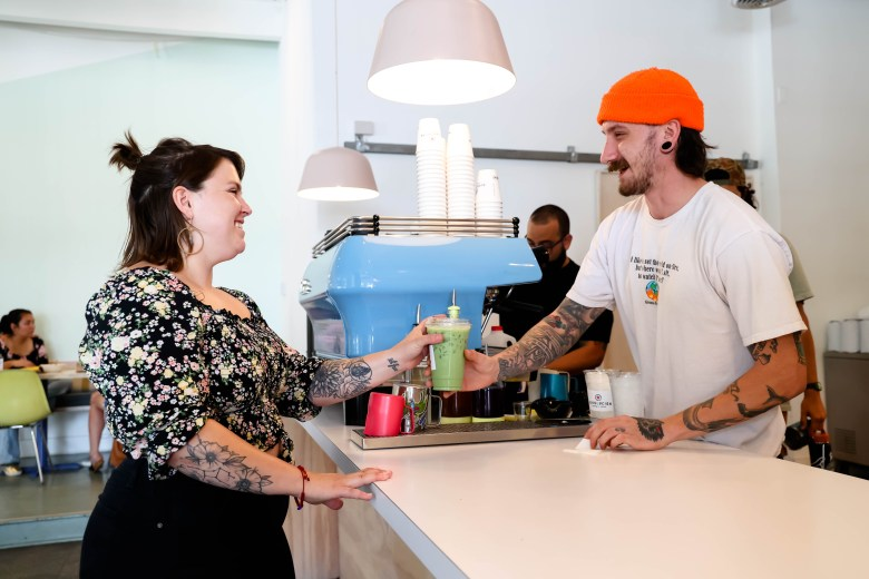 Josh Kangas hands Warden her usual order of a Matcha Latte at Revolucion Coffee. Warden loves working there and having meetings with clients.