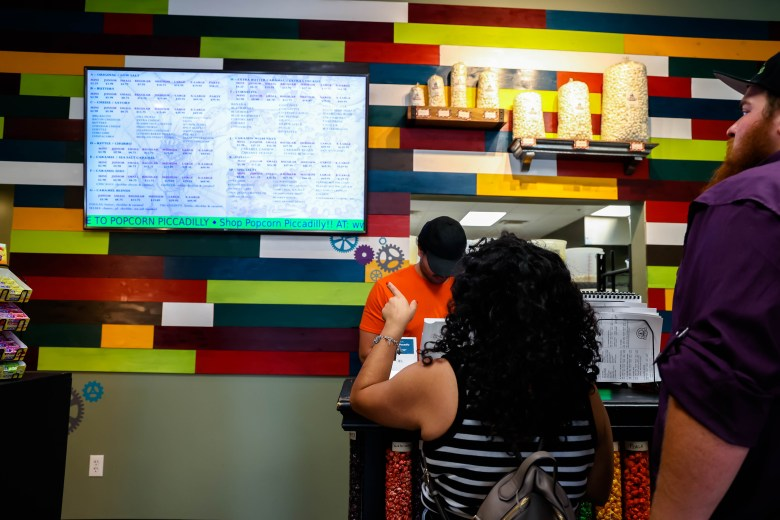 Valerie and Zach pick from an expansive list of flavors at Popcorn Picadilly.