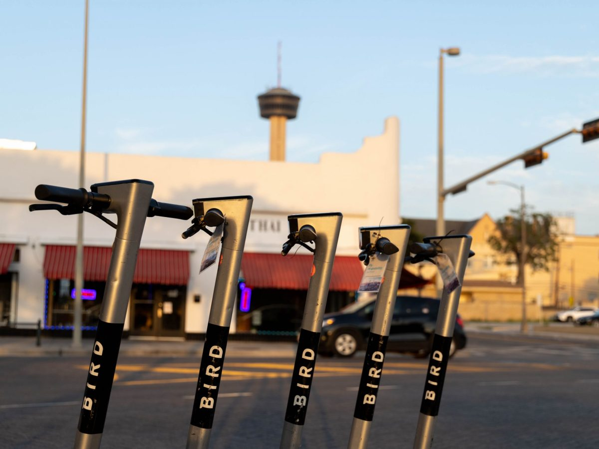 The Tower of the Americas is seen behind a row of Bird scooters on Tuesday.