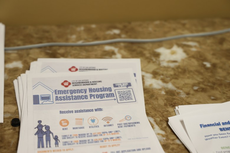A flyer with information about the Emergency Housing Assistance Program sits on the desk inside of the evictions outreach office at the Justice of the Peace Precinct Two building.