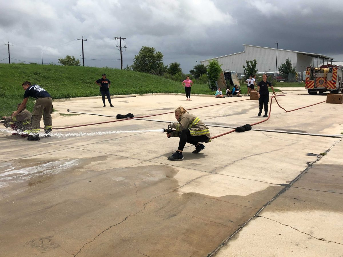 #HeroLikeHer participants simulate what it might be like on the scene of a fire by climbing over obstacles and trying to knock over the orange pylon with the fire hose.