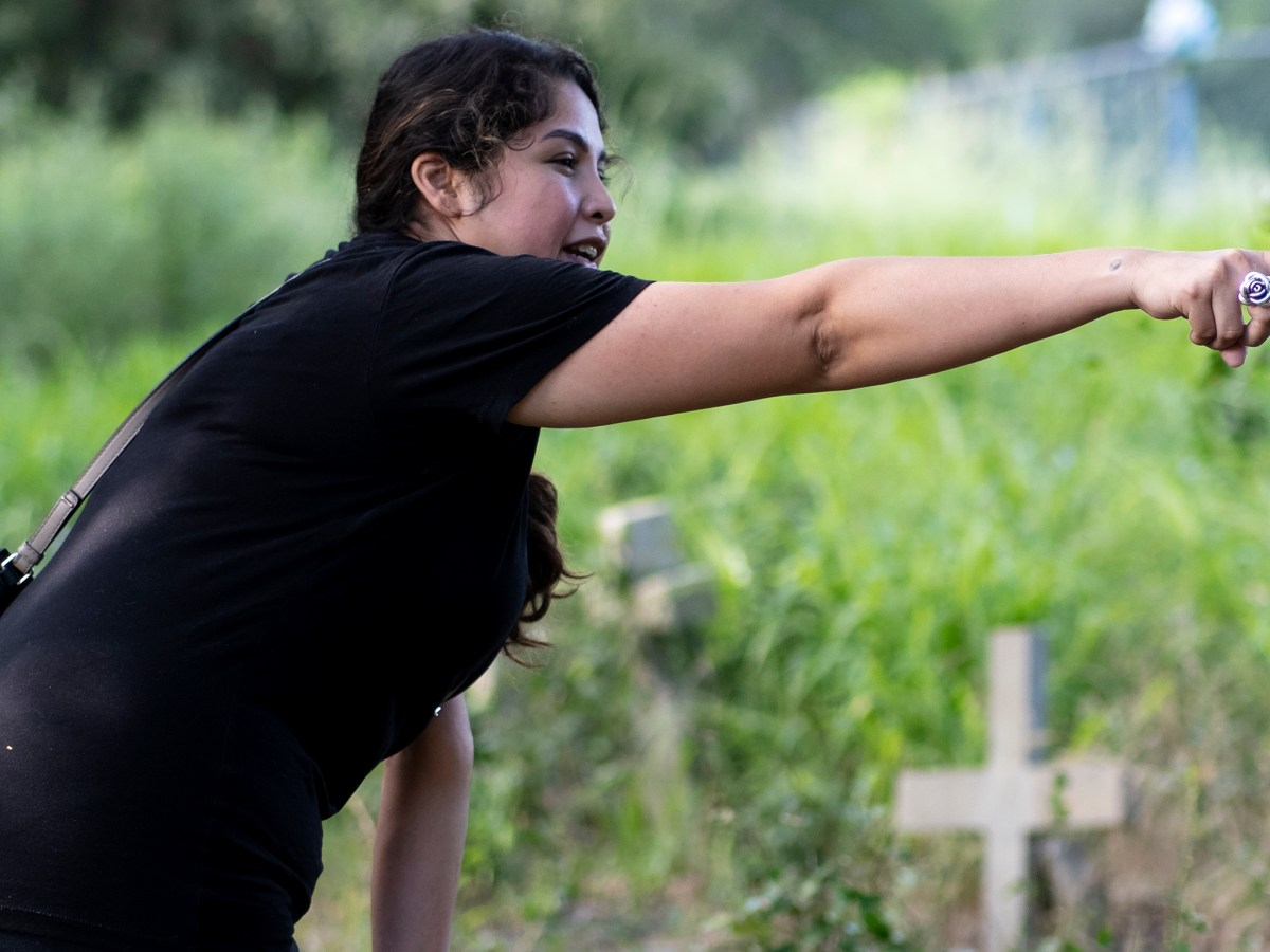 Rose Hernandez points to a headstone covered by overgrown weeds and trees in Guadalupe County on Sunday.
