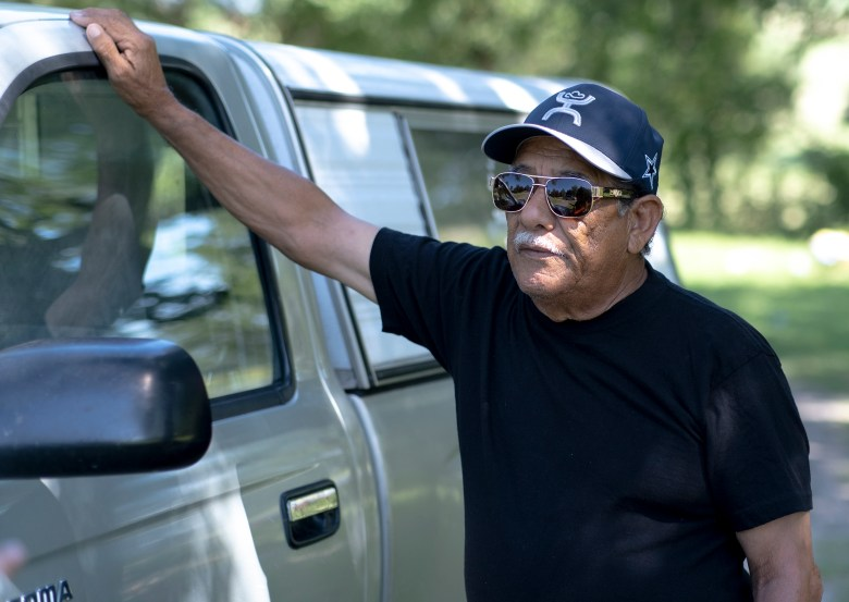 Erneto Gonzales leans against his pickup truck after working at San Pablo cemetery outside of Lockhart on Sunday.