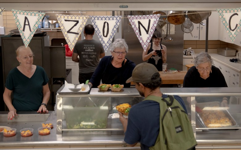 Carol McConnell, center, serves lunch to a homeless man at Café Corazón on Wednesday.