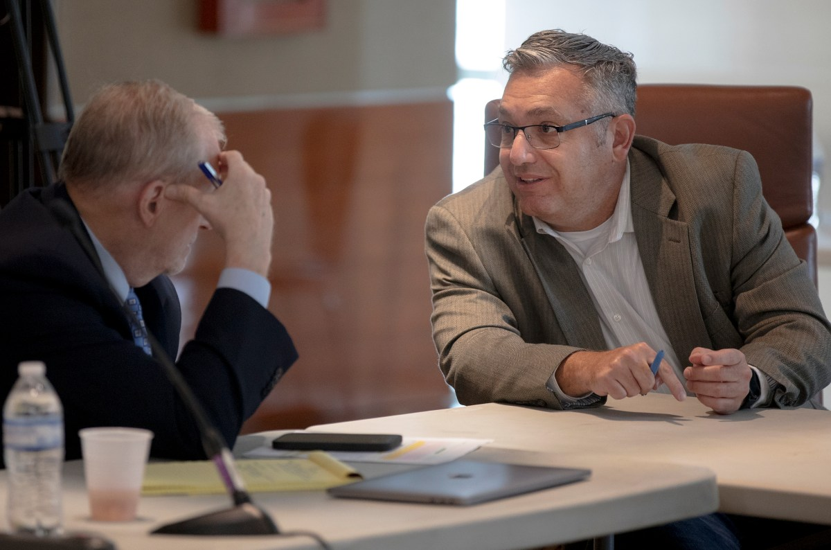 Christopher Lutton, chair of union negotiations committee, talks with Ron DeLord, an attorney representing the police union, during collective bargaining negotiations between the City and police union on Thursday.