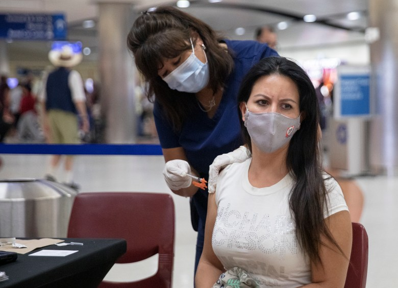 Leticia Negrete, of Mexico City, receives a COVID-19 vaccine from Celia Torres, a registered nurse with Curative, during a vaccination pop-up clinic at the San Antonio International Airport on Wednesday. Negrete had just landed on a flight from Mexico City when she opted to receive a vaccine.