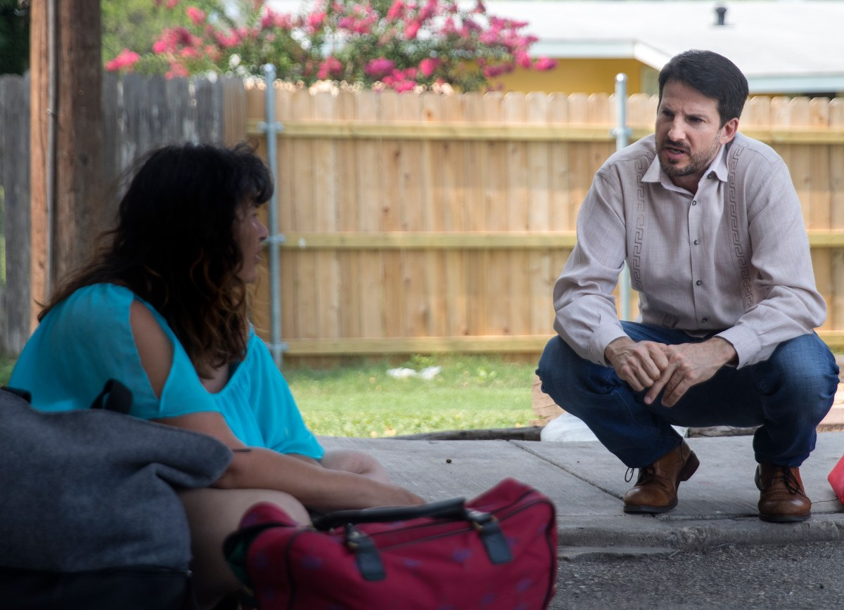 City Council member Mario Bravo (D1) speaks to a homeless woman, who wished to remain anonymous, outside of his field office on Wednesday.