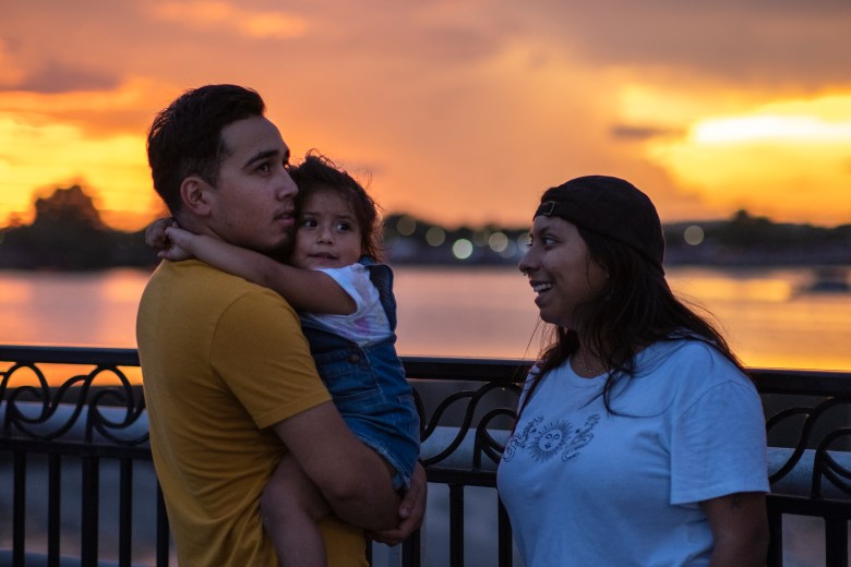 Jacob Aleman holds his daughter, Aria, alongside to Gladys Ramirez as they watch fireworks exploding over the neighborhood during the Fourth of July Celebration at Woodlawn Lake Park on Sunday.