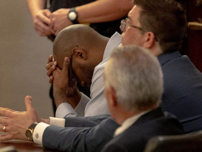 Otis McKane holds his head after hearing jury's verdict declaring him guilty of capital murder during his trial on Monday.