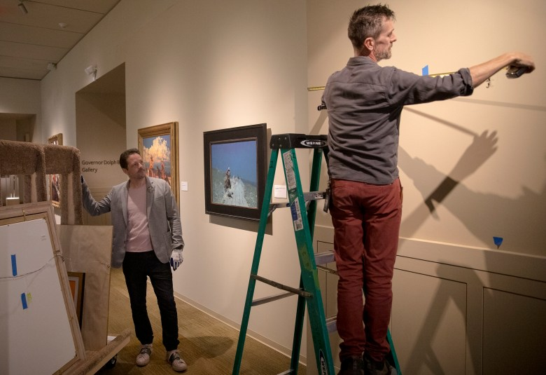 Jason Kirkland, exhibition manager at the Briscoe Western Art Museum, left, watches Aidan Furey prepare a wall for a painting on Tuesday.