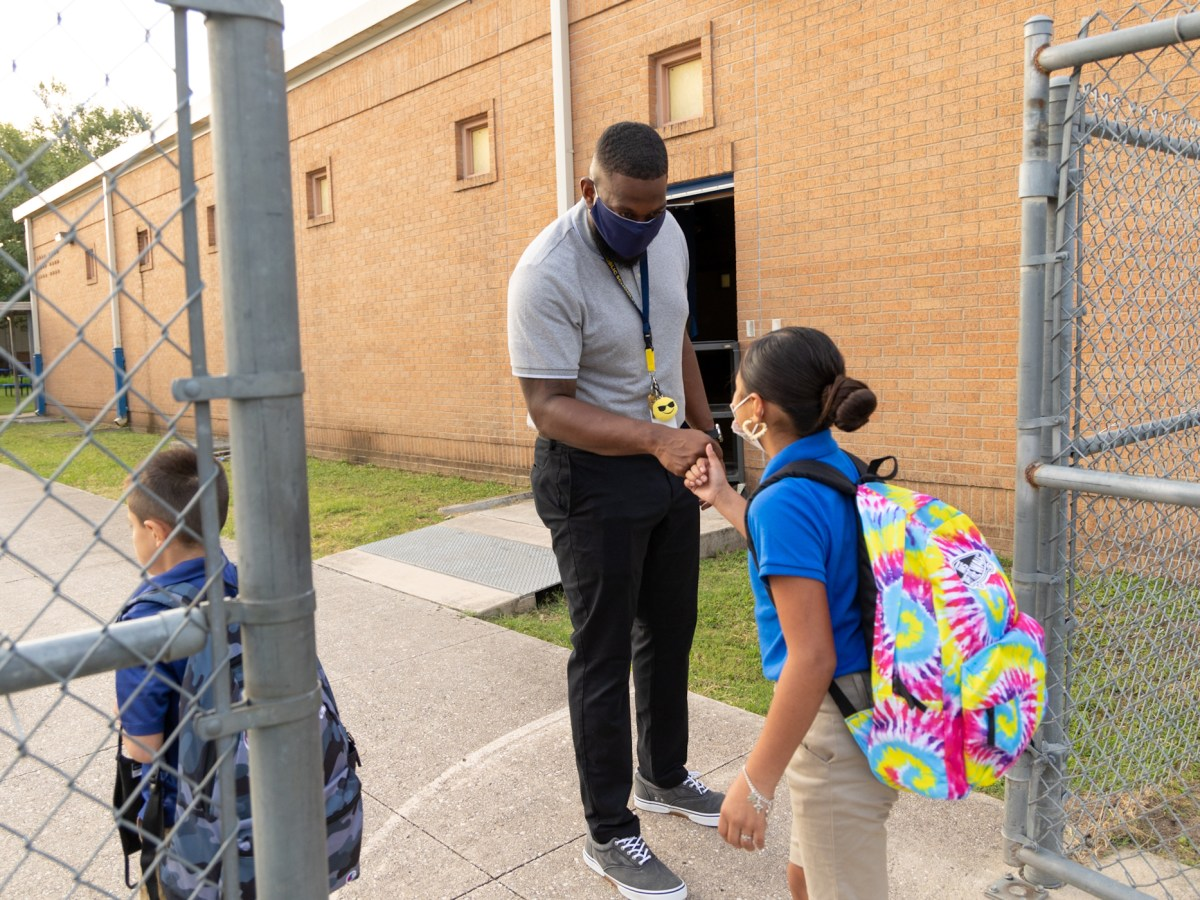Democracy Prep Dream Coach Derek Lockhart greets students as they arrive for their first day of school.