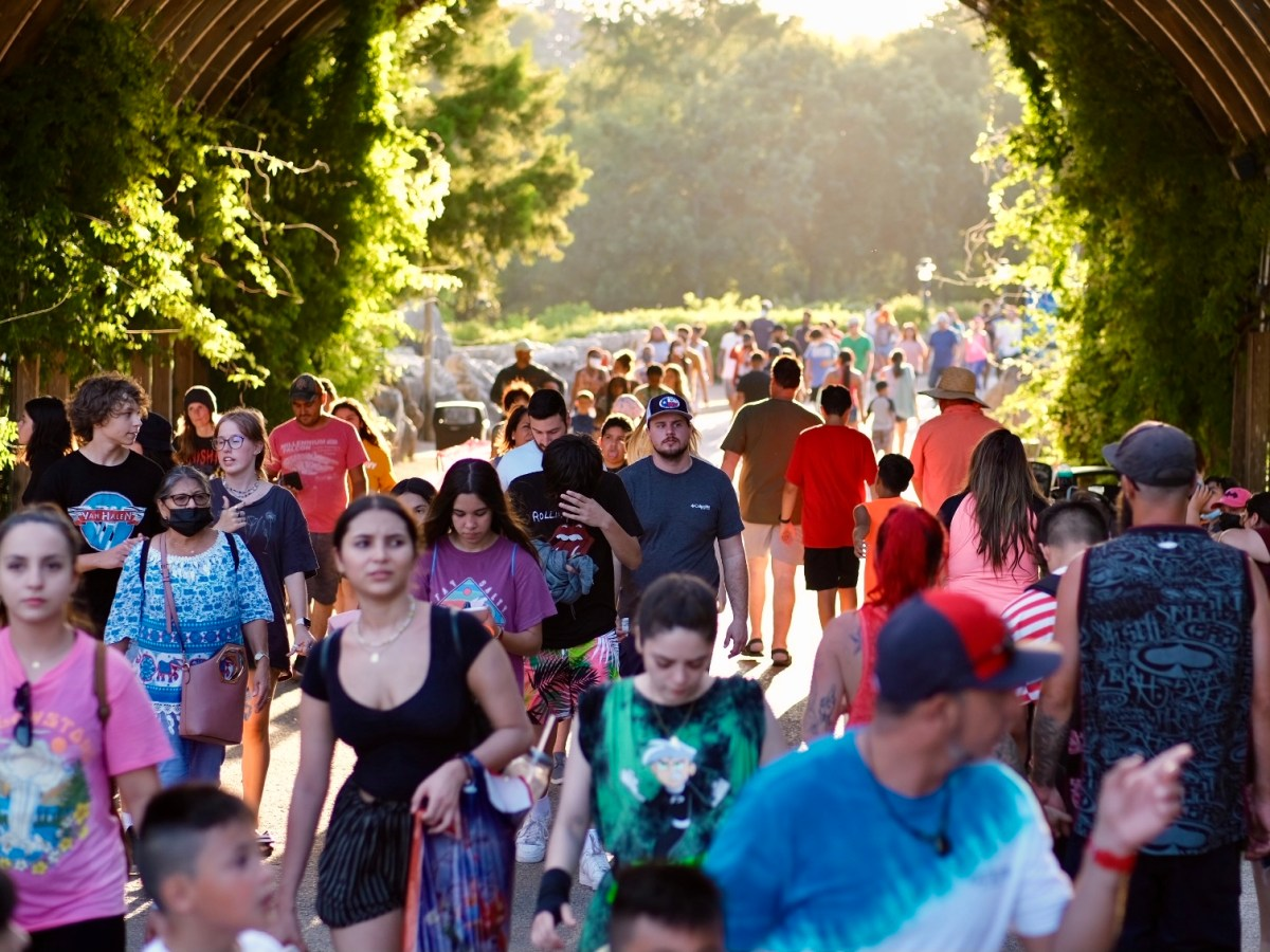 People walk through Six Flags Fiesta Texas on Saturday. The theme park was forced to cancel its popular Celebrity Fan Fest event due to a new surge of COVID-19 cases caused by the Delta variant.