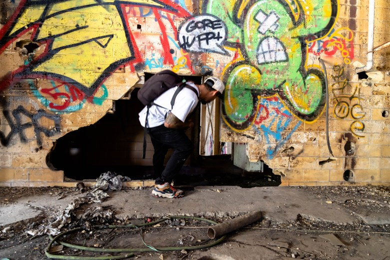 Martinez ducks to walk through a hole in a crumbling wall inside of the Lone Star Brewery.