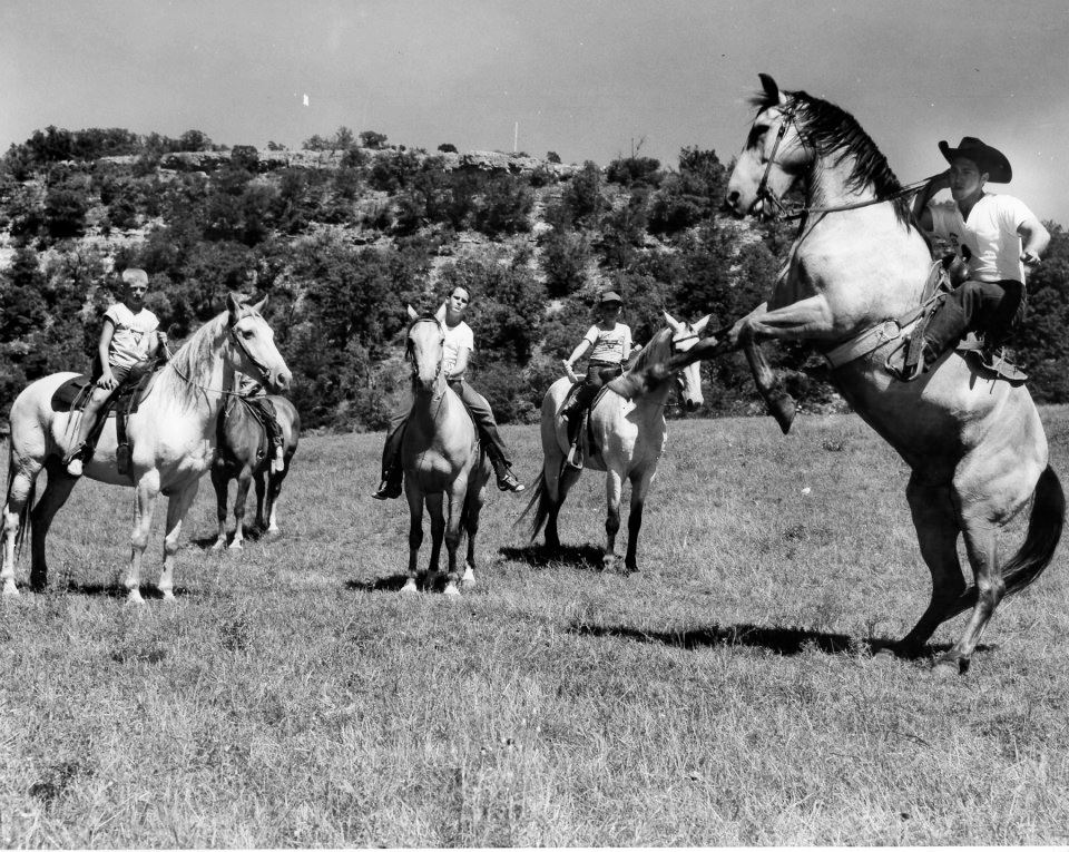 An archived photograph, the date of which is unknown, shows campers riding horseback at Camp Flaming Arrow.