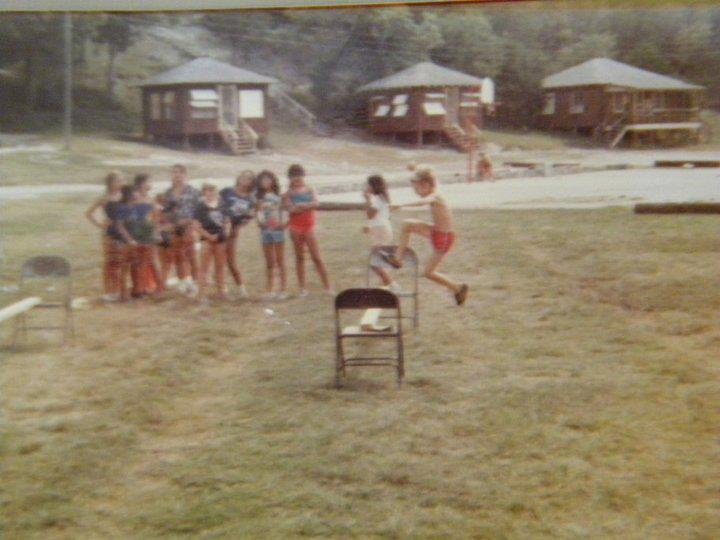 Campers jump over homemade hurdles made of a wooden beam suspended between two folding chairs.