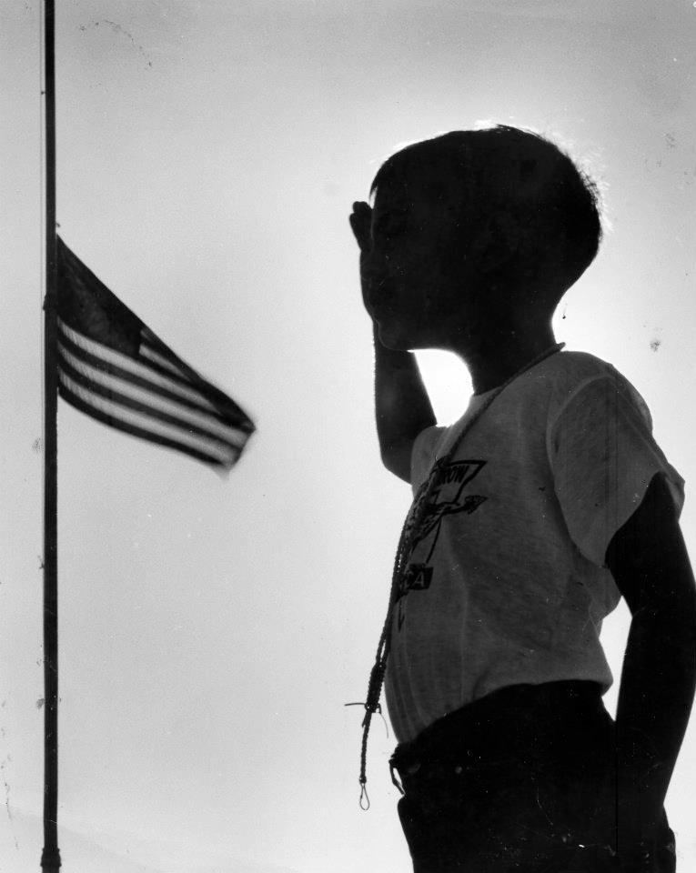 A young boy salutes to the flag at Camp Flaming Arrow.
