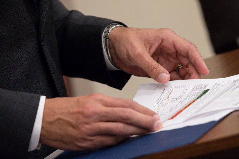 Mayor Ron Nirenberg flips through local COVID-19 infection rates while answering questions during the press conference.