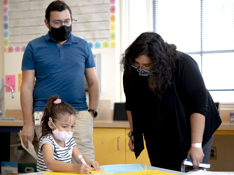 Isabella Polasek helps her mom, Sabrina Macal-Polasek, fill out their student drop-off and pick-up pass during a back to school event at Advanced Learning Academy on Thursday.
