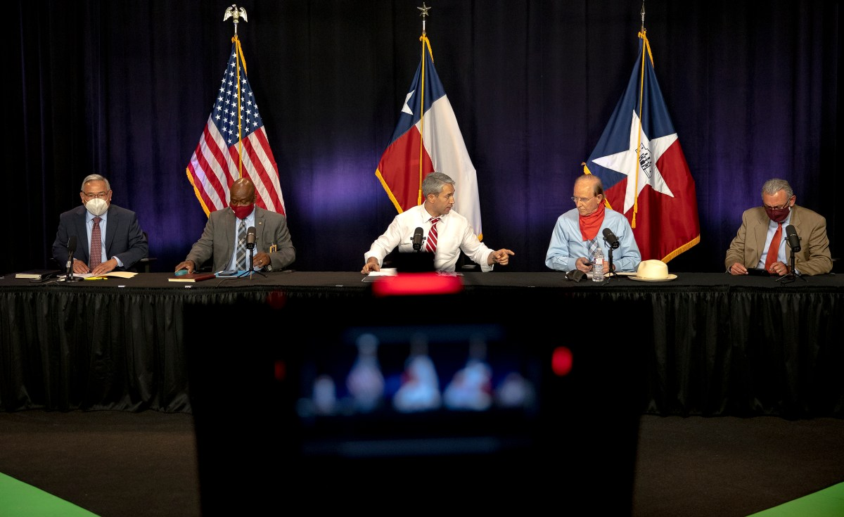 Mayor Ron Nirenberg, center, talks to Bexar County Judge Nelson Wolff before a COVID-19 briefing on Tuesday.