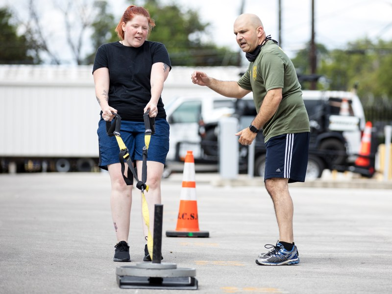 Sheriff Javier Salazar encourages job candidate Cheyenne Stevens as she participates in a fitness exam during a recruitment event hosted by the Bexar County sheriff's office on Saturday.