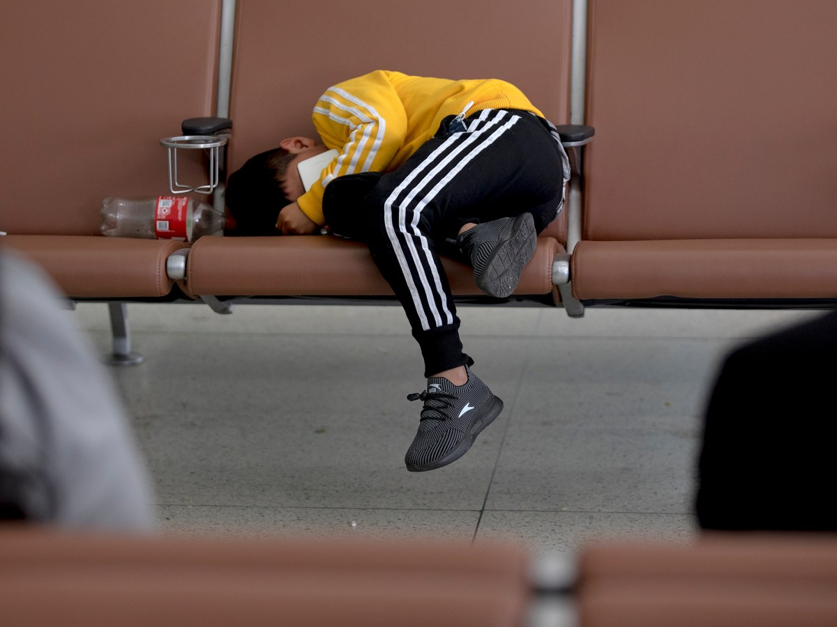 A young migrant boy sleeps on a chair across from his parents at the San Antonio International Airport on Saturday.