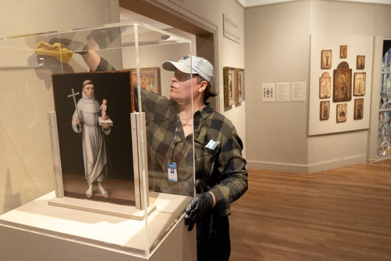 Cherise 'Rhys' Munro carefully dusts an artwork enclosure at the McNay Art Museum where she works as an art conservator.