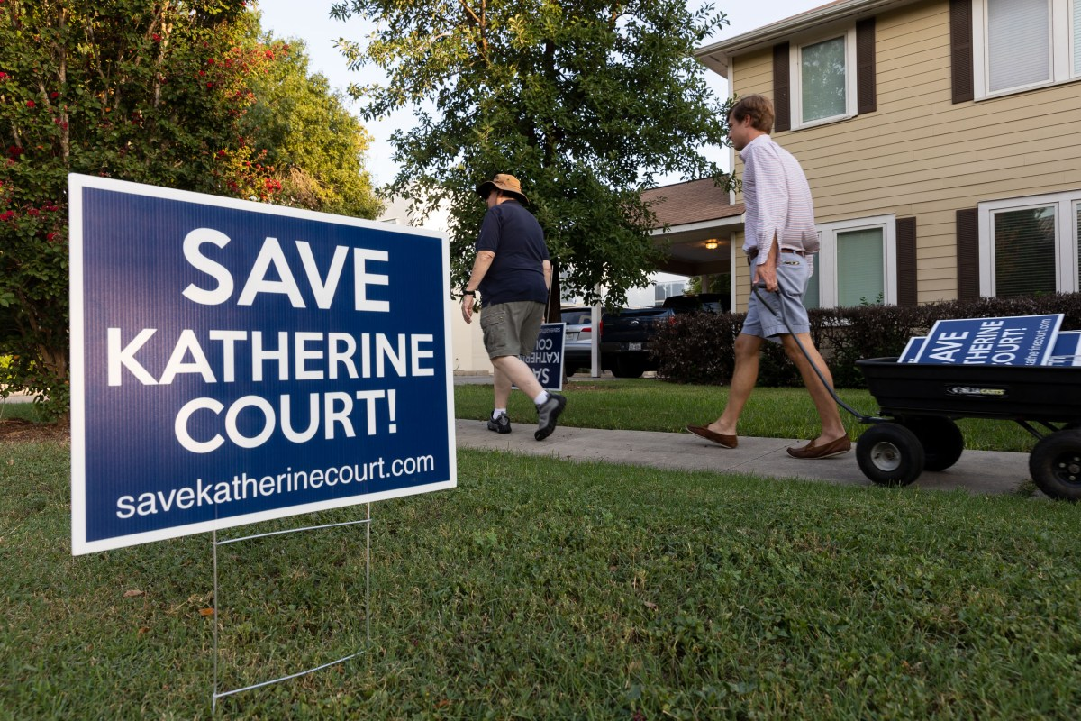 Katherine Court residents John Feitshans, left, and Mike Wargovich place signs opposing a proposed housing development on the Alamo Heights street.