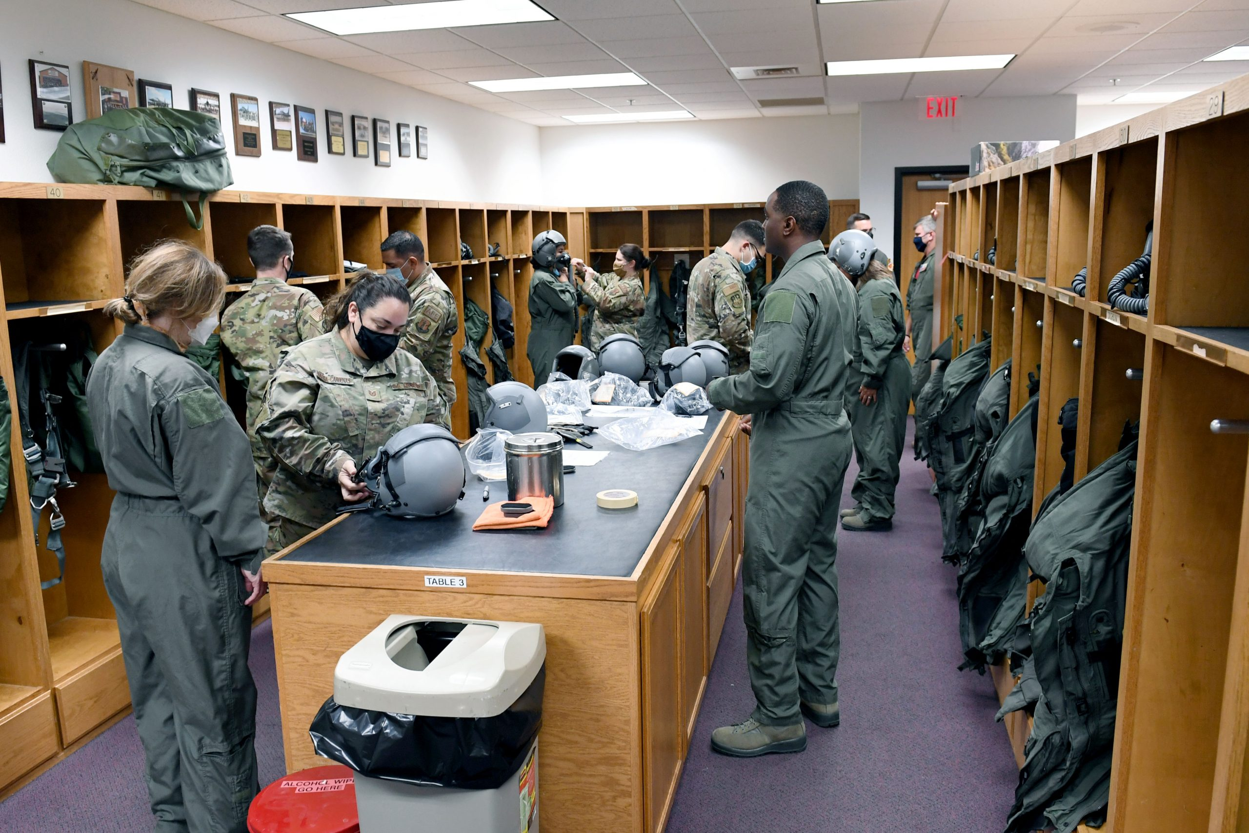Air Force personnel help outfit spouses for a high-speed taxiing experience in an F-16 fighter jet.
