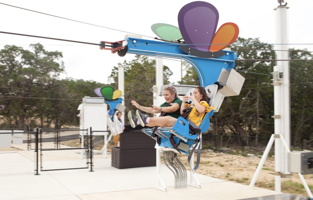 Brooke Kearney, left, chief mission officer with Morgan's Wonderland rides the new zip line at Morgan's Wonderland Camp with Briana Troy.